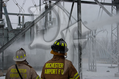 The Chief & a firefighter from the Rochester Airport Fire Dept. watch as a 3rd airport firefighter uses the roof turret on Rescue 4, a crash truck from the Greater Rochester international Airport (GRIA), to continue cooling a large transformer after a fire on January 14, 2012.