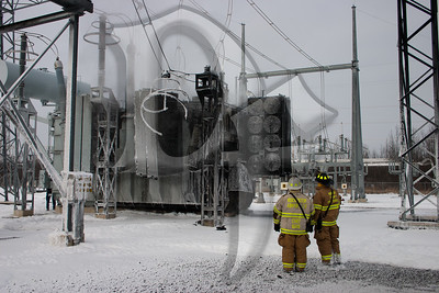 Fire officials survey the damage to a large transformer after a fire on January 14, 2012.