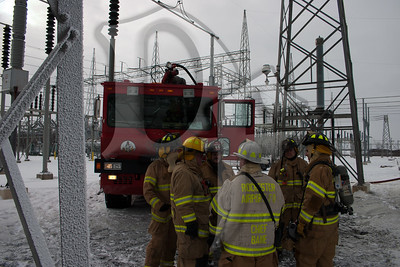 Firefighters from the Henrietta and Rochester Airport Fire Dept's discuss their next move after extinguishing a fire in a large transformer on January 14, 2012.