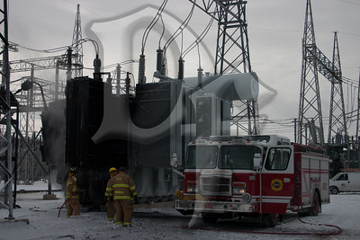 Henrietta firefighters use a booster line to finish cooling a large transformer following a fire on January 14, 2012.