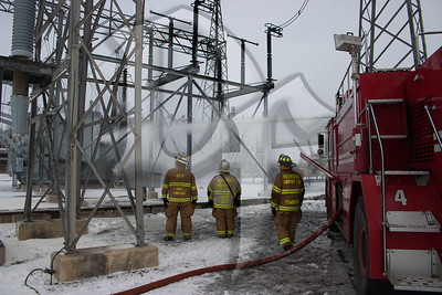 The Chiefs of the Henrietta & Airport Fire Departments, along with a firefighter from the Rochester Airport Fire Dept. watch as a 3rd airport firefighter uses the roof turret on Rescue 4, a crash truck from the Greater Rochester international Airport (GRIA), to continue cooling a large transformer after a fire on January 14, 2012.