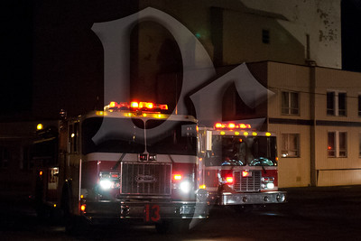 A pair of fire engines from the Rochester Fire Department are staged at the scene of a 3rd alarm building fire on Emerson St. February 24, 2012