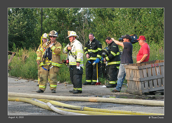 Chiefs from mutual aid departments consult as a news cameraman records the scene.
