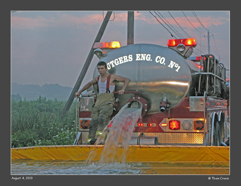 A tanker from the Johnson Fire Department empties its load to a portable pool.