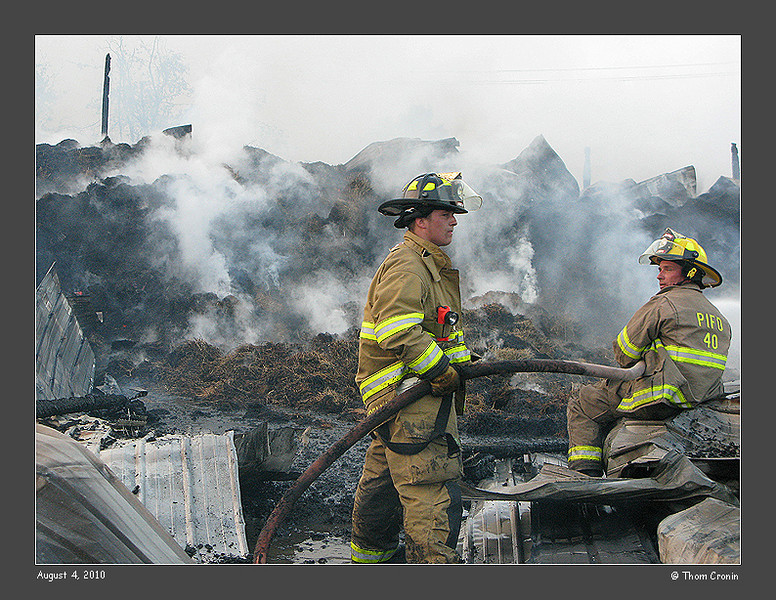 Pine Island firefighters hose down hot spots in a pile of hay.