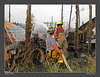 Two Pine Island firefighters operate a line during overhaul.  Note the burned tractors in the foreground.