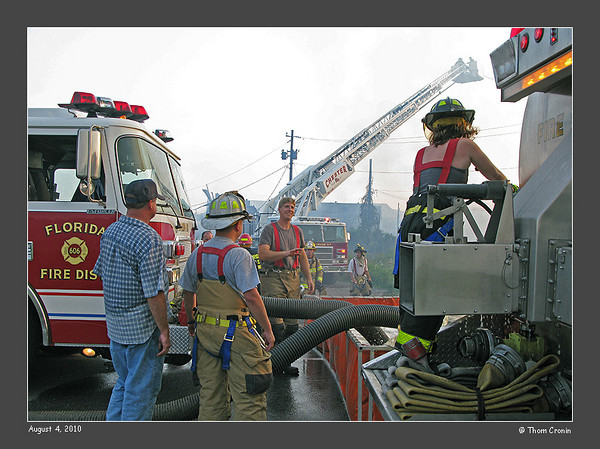 A tanker unloads its water to a portable pool supplying Florida's pumper.  Chester's tower ladder operates in the background.