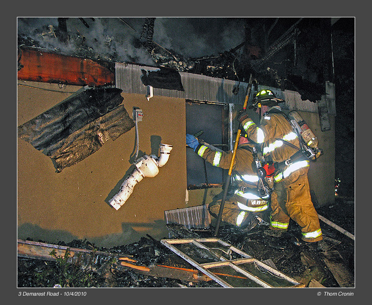 Firefighters John Miles right, and John VanWoudenberg kneeling, extinguish hot spots in the basement level of the  structure.