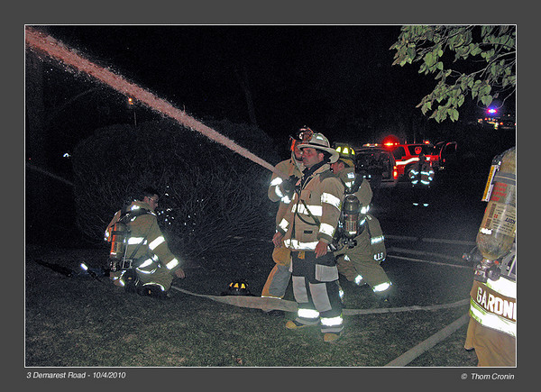 Greenwood Lake Chief John Rader directs a hose crew operating a 2 1/2 inch hand line as they darken down fire impinging on power lines attached to the building.  The effort succeeded in keeping the wires from burning off the house.  Downed power lines are a major hazard for firefighters.