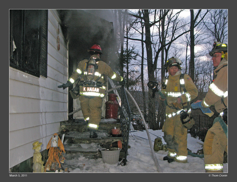 Firefighters Roche and Lyons stand ready with a back-up line at the front door.