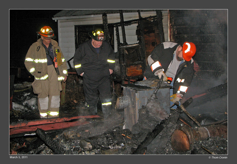 Orange County Fire Investigators John Orr (right) and Jeff Hunt (center) examine the coal stove while Orange County Deputy Fire Coordinator Charlie Niemann looks on.