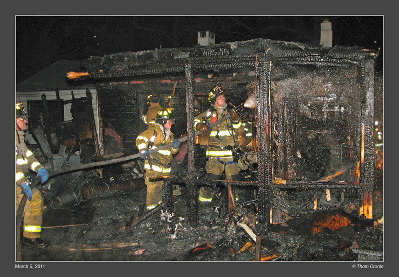 Left to right, firefighters T.J. Lyons, Kristen Schork and Brendan Donohue extinguish hot spots on the number 3 side.