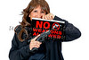 Middle Aged Woman holding a No Weapons Sign and a Handgun
