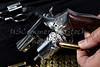 Man loading compact magnum revolver firearm Closeup