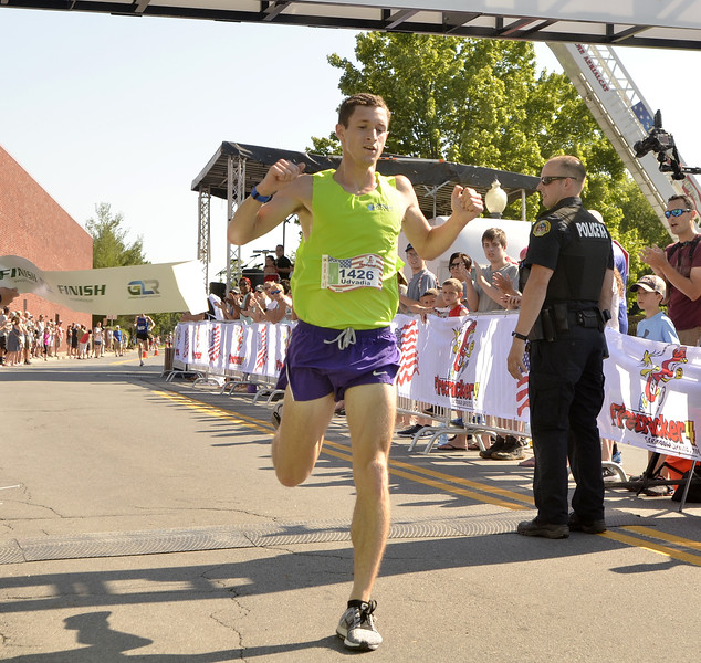STAN HUDY - SHUDY@DIGITALFIRSTMEDIA.COM<br /> Former UAlbany runner Ryan Udvadia breaks the tape as the overall winner of Wednesday's Firecracker 4 4-mile race through historic Saratoga Springs.