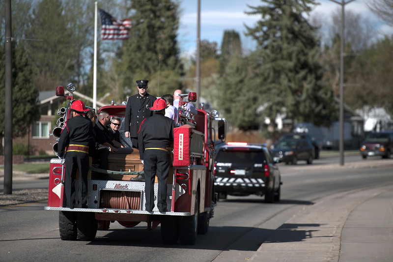 Friends and family of former Loveland Fire Rescue Authority Fire Marshal Tim Haag ride with the casket in the back of an antique fire truck during the funeral procession along Eisenhower Boulevard on Wednesday 19, April 2017, in Loveland.  (Photo by Logan O'Brien/Loveland Reporter-Herald)
