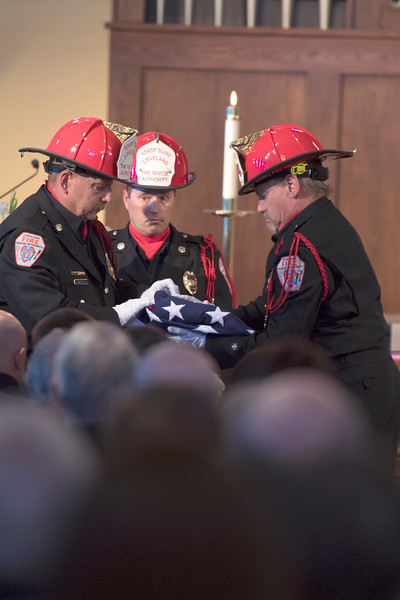 Members of the Loveland Fire Rescue Authority Honor Guard fold the flag during the service of Timothy Haag at the Zion Lutheran Church in Loveland on Wednesday 19, April 2017.  (Photo by Logan O'Brien/Loveland Reporter-Herald)