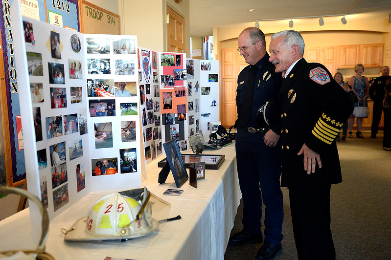 Loveland Fire Rescue Authority chief Mark Miller, right, and Lt. Randy Stuart look at photos Wednesday, April 18, 2017, during former LFRA fire marshall Tim Haag's memorial service at Zion Lutheran Church in Loveland.  (Photo by Jenny Sparks/Loveland Reporter-Herald)