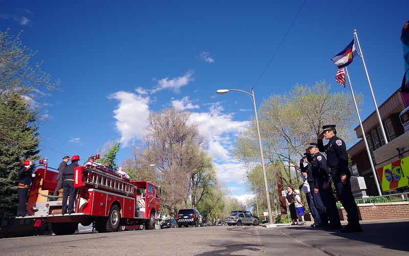 Loveland Fire Rescue Authority firefighters salute Wednesday, April 18, 2017, as an antique fire truck carries the casket of former LFRA fire marshall Tim Haag past fire station 1 in downtown Loveland after Haag's memorial service. (Photo by Jeff Stahla/Loveland Reporter-Herald)