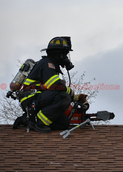 A CHFD Firefighter getting ready to open up the roof of a house with an attic fire.