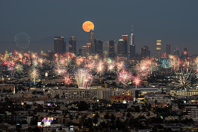 Full moon rising over Los Angeles on the 4th of July as fireworks fill the sky