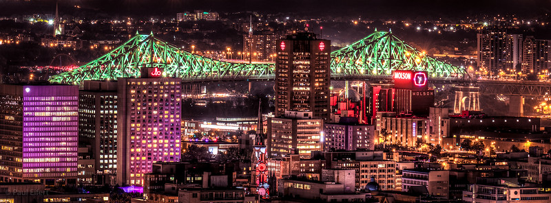The Jacques Cartier Bridge in Montreal is lit up in green on a summer evening in 2017.