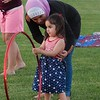 Sarah Akaabi, 12, and her 2-year-old sister Tamarah Akaabi, keep themselves busy before the fireworks start for the Fourth of July celebration at LeLacheur Park. Sun/Aaron Curtis
