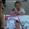 Susan Festa, of Boston Caricature, draws 5-year-old Sam Field, of Westford, as Superman, shortly before the July Fourth fireworks start at LeLacheur Park. Sun/Aaron Curtis