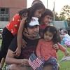 From left, 6-year-old Surabhi Khandekar, 4-year-old Reyamsh Shrma, and 19-month-old Keya Khandekar, pile on top of Abhinab Sherma, before the fireworks start at LeLacheur Park on the Fourth of July. Sun/Aaron Curtis