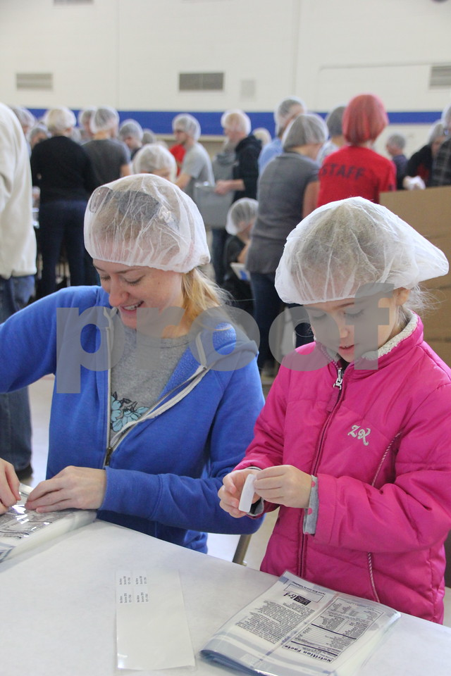 Saturday, December 5, 2015, Fort Dodge Christian Community School put on their 1st Annual Packing Meals for Starving Children event. At the time these pictures were being taken, there were 178 volunteers on hand not including those volunteering in others areas not involving packing the meals. Pictured here (left to right) is : Emily McCullough, and daughter, Eliza McCullough working in the label section of the process.
