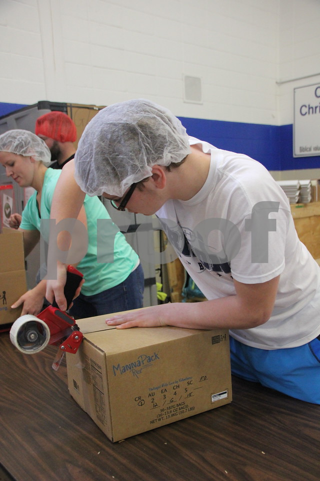 Geoff Astor seals packed boxes. Saturday, December 5, 2015, Fort Dodge Christian Community School put on their 1st Annual Packing Meals for Starving Children event. The event was staged in the school gymnasium.