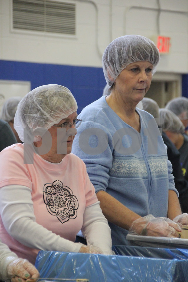 Pictured (left to right) is: Bev Longnecker, and Holly Legg, bagging rice to be sealed and packed into boxes. Saturday, December 5, 2015, Fort Dodge Christian Community School put on their 1st Annual Packing Meals for Starving Children event. The school gymnasium was the staging area for the packing.