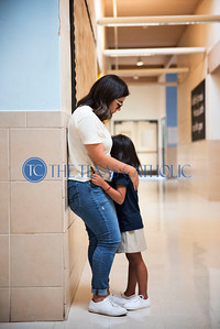 An unidentified mother comforts her daughter and tries to ease her worries on the first day of school at Santa Clara of Assisi Catholic Academy Aug. 8.