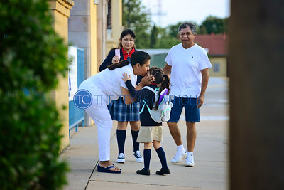 Maria Gallo kisses her granddaughter Linda Garcia goodbye on the first day of school Aug. 8 at Santa Clara of Assisi Catholic School.