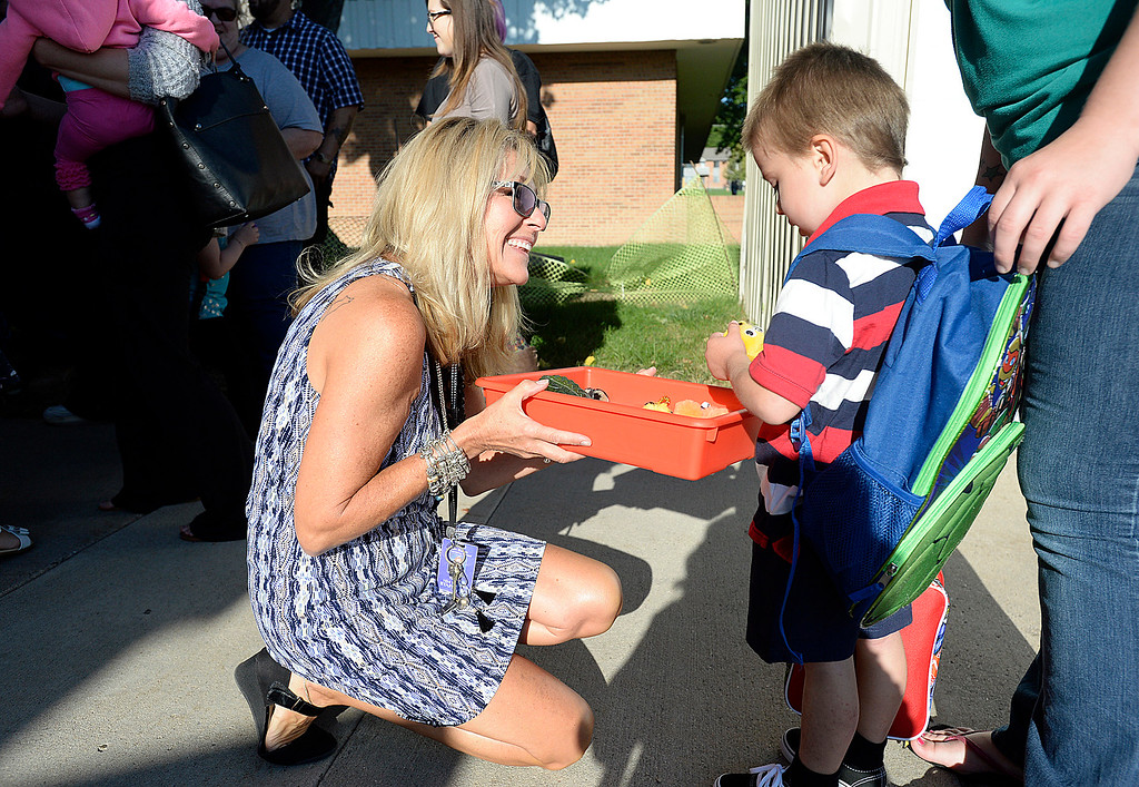 . Kindergarten teacher Karey Thomas lets Nathan Barnes, 4, pick out one of her hand-made quiet critters Friday, Aug. 18, 2017, before heading inside to start his first day of school at Van Buren Elementary School in Loveland. Thomas gave the critters to her students to make them feel more comfortable.  (Photo by Jenny Sparks/Loveland Reporter-Herald)