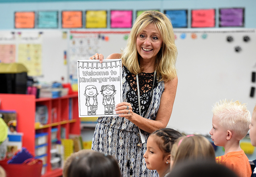 . Kindergarten teacher Karey Thomas gives out a coloring sheet to students Friday, Aug. 18, 2017, on the first day of school at Van Buren Elementary School in Loveland.   (Photo by Jenny Sparks/Loveland Reporter-Herald)