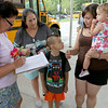Crocker Elementary School art teacher Andrea Oullette helps out second grader Dexter Loder, 7, and his grandmother Gail Majors, mom Farah Fields and his sister Evalet Barrett, 1, on the first day of school in Fitchburg Thursday. SENTINEL & ENTERPRISE/JOHN LOVE