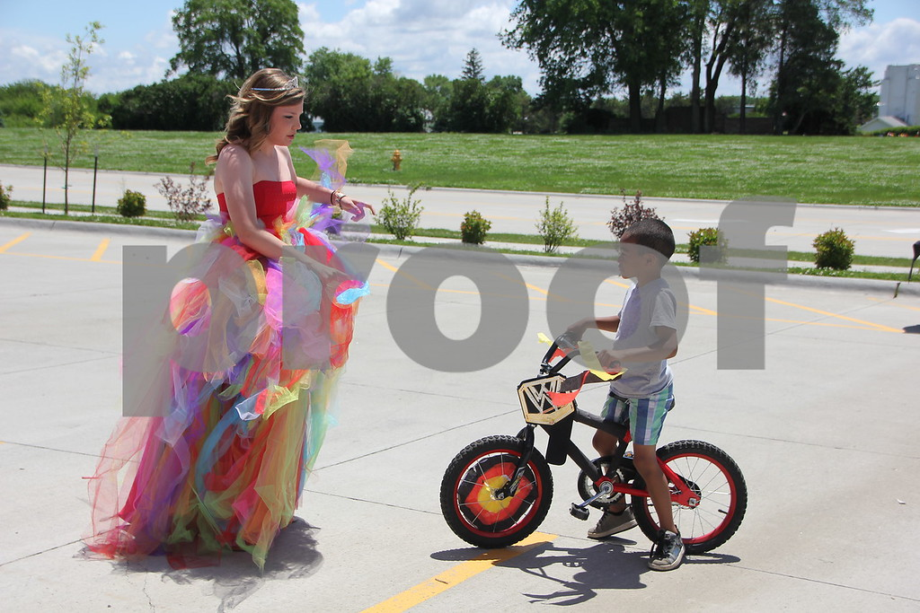 Rebecca Gerdes instructs Amari McCaleb, an entrant in the Pedal Parade event,  in bicycle safety at Fort Frenzy's first Pedal Parade event held in the parking lot at Fort Frenzy on Sunday, June 7, 2015. Amari just couldn't wait to get riding his bike.