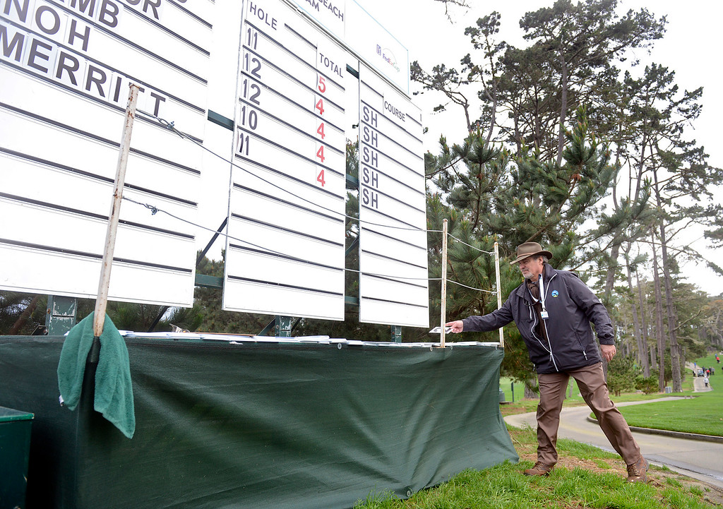 . Score board volunteer Steve Beckwith of Arizona grabs a number that flew off due to high winds at Spyglass Hill Golf Course during the AT&T Pebble Beach Pro-AM in Pebble Beach on Thursday February 9, 2017. (David Royal - Monterey Herald)