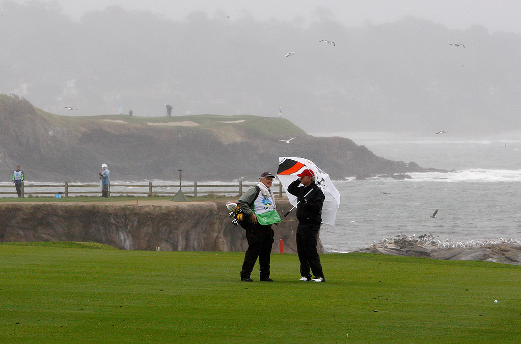 . Amateur player David Gill and caddy battle rain and wind while playing the 18th hole at the Pebble Beach Golf Links during the first round of the AT&T Pebble Beach Pro Am on Thursday, Feb. 9, 2017.   (Vern Fisher - Monterey Herald)