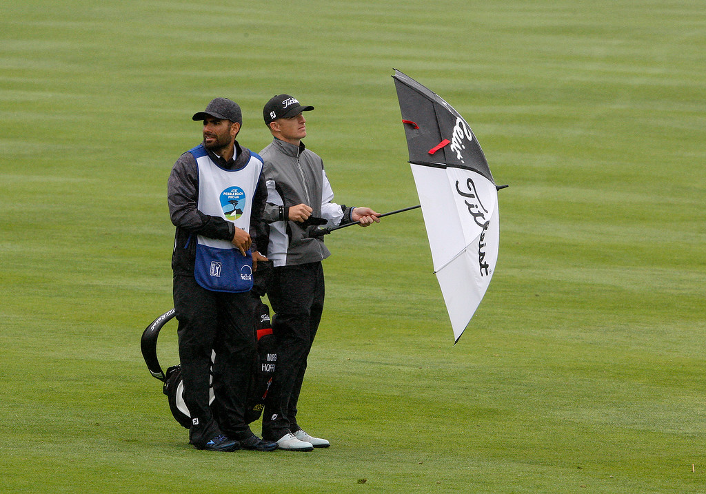 . Morgan Hoffmann and caddy battle rain and wind while playing the 18th hole at the Pebble Beach Golf Links during the first round of the AT&T Pebble Beach Pro Am on Thursday, Feb. 9, 2017.   (Vern Fisher - Monterey Herald)