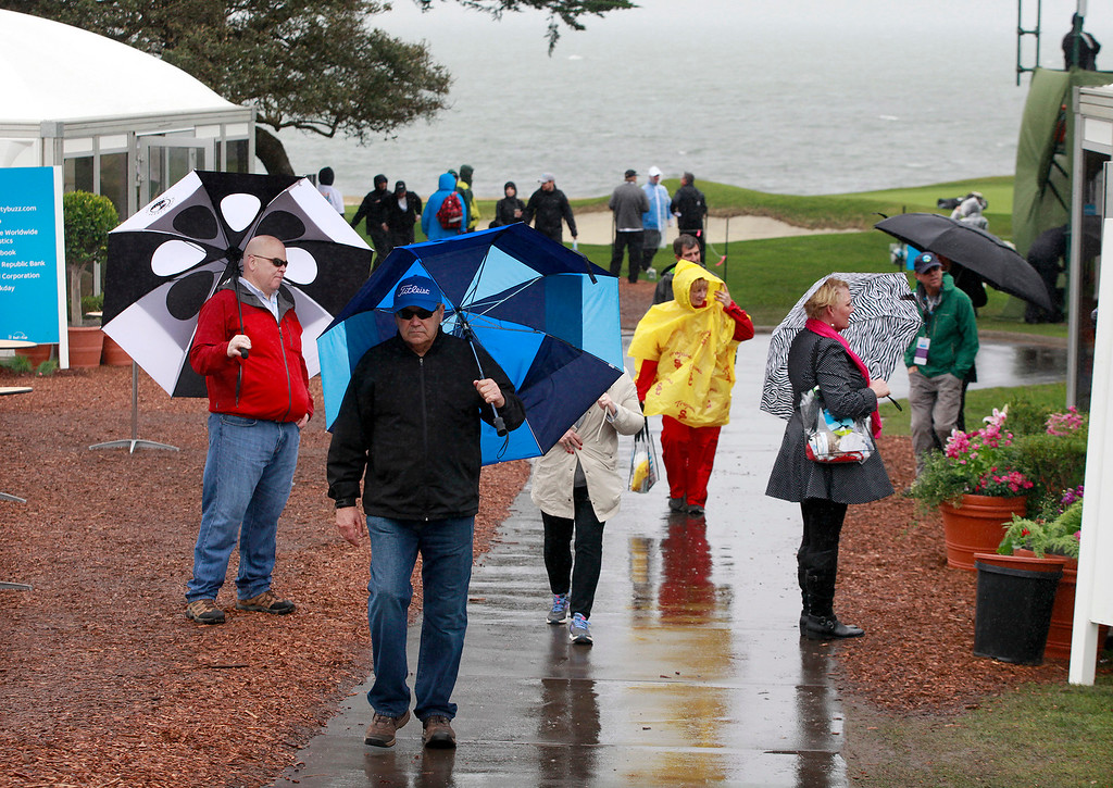 . Patrons deal with the wind and rain while watching the action at the 18th hole at the Pebble Beach Golf Links during the first round of the AT&T Pebble Beach Pro Am on Thursday, Feb. 9, 2017.   (Vern Fisher - Monterey Herald)