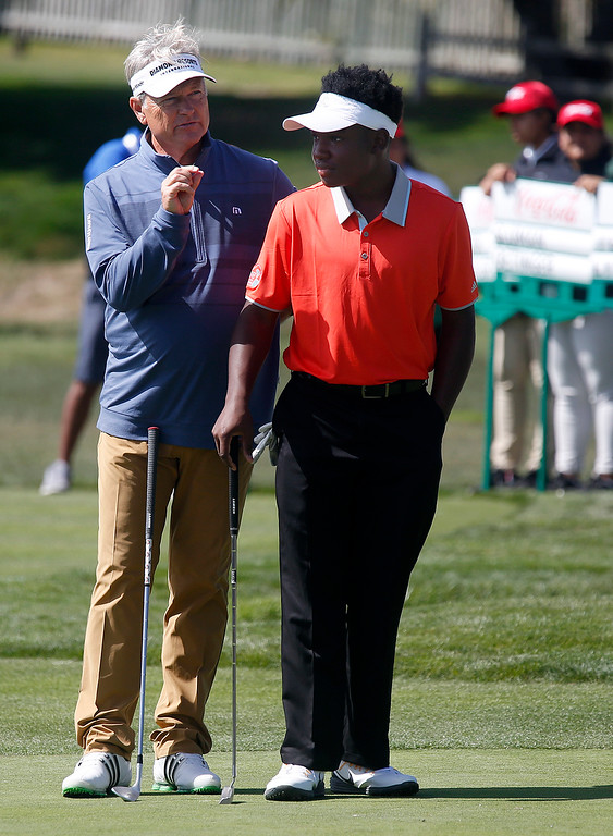 . PGA player of this John Cook gives junior player of Kambron Taylor from The First Tee of Augusta tips before his putt on the second hole during the Coca-Cola Champions Challenge at Pebble Beach Golf Links  on Thursday September 21, 2017. Teams competed for a $40,000 charity purse playing a modified Scotch, alternate-shot format on holes 1, 2, 3, 17 and 18. (David Royal/Herald Correspondent)