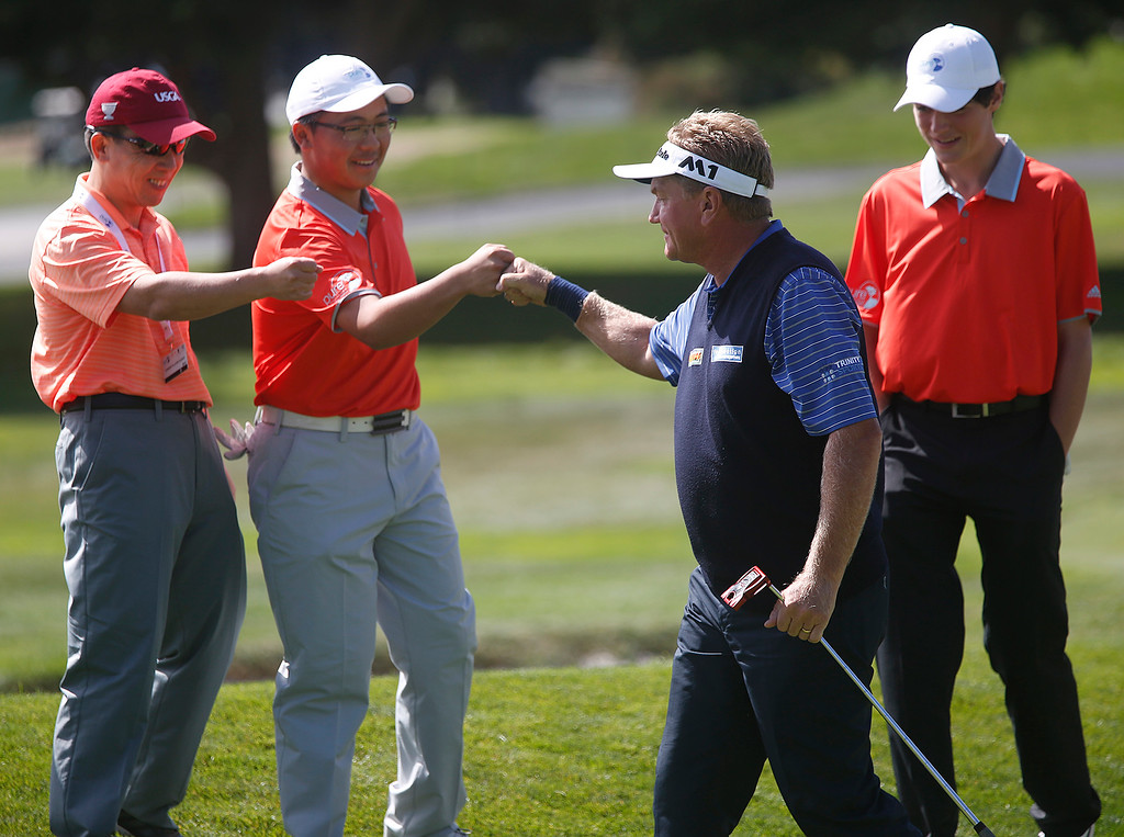 . PGA player Paul Broadhurst bumps fists with junior partner Michael Shaw of The First Tee of the Tri-Valley after sinking his putt to win the second hole during the Coca-Cola Champions Challenge at Pebble Beach Golf Links  on Thursday September 21, 2017. Teams competed for a $40,000 charity purse playing a modified Scotch, alternate-shot format on holes 1, 2, 3, 17 and 18. Broadhurst and Shaw won the first three holes. (David Royal/Herald Correspondent)