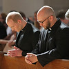 Matthew Donovan and Eric Immel bow their heads for a moment of prayer during the First Vows ceremony on August 10, 2013, at St. Thomas More Parish in St. Paul, Minnesota.