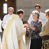 Fr. Timothy Kesicki, SJ, receives the gifts presented by family of Eric Immel and Matthew Donovan at the First Vows ceremony at the St. Thomas More Parish in St. Paul, Minnesota, on August 10, 2013.
