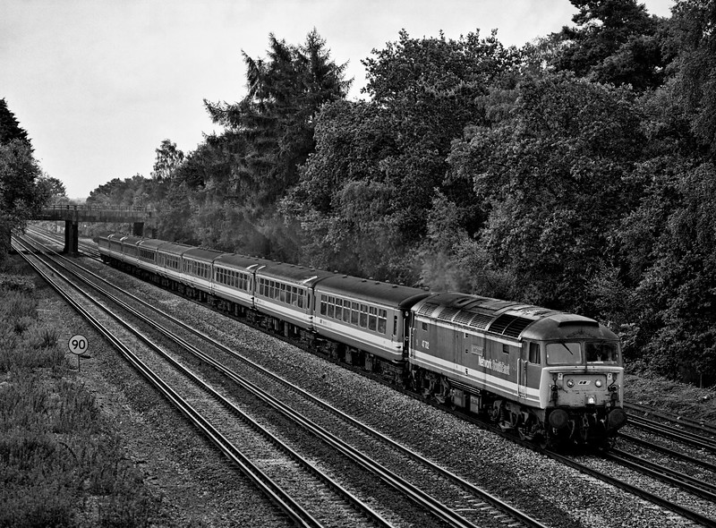 47702 passes Pirbright Junction with the 17:05 Waterloo - Yeovil Junction on 9th July 1993. This was the final loco-hauled M-F service on the Waterloo - Exeter route. Scanned negative.