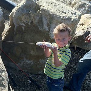 A little one enjoys catching fish during Free Fishing Day at Carbon County Pond. Photo taken 6-7-14 by Brent Stettler, Utah Division of Wildlife Resources.