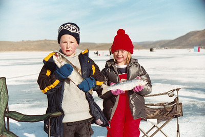 Boy and girl ice fishing at Scofield Reservoir, Utah
