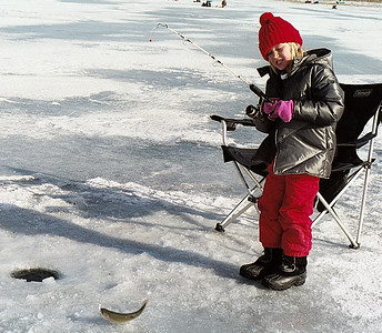 A young girl yanks a small trout onto the ice at Scofield Reservoir. Photo taken 6-26-2007 by Brent Stettler, Utah Division of Wildlife Resources.